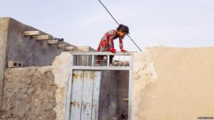 A girl plays on the roof of her house in a small village near Laft