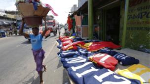 A woman with a box of clothes on her head walks past a stall selling football jerseys, Abidjan, Ivory Coast - Tuesday 3 June 2014.