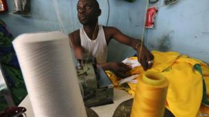 An employee sews football jerseys at a workshop in the Adjame district of Abidjan, Ivory Coast - Tuesday 3 June 2014.