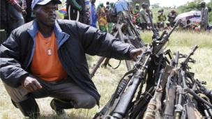 A FDLR rebel squatting next to a pile of surrendered arms in Kateku, DR Congo - Friday 30 May 2014