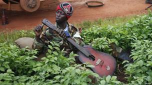 A Seleka fighter fixing his guitar in village between Bambari and Grimari in CAR - Saturday 31 May 2014