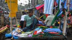Flags and jerseys being sold at a Dhaka market