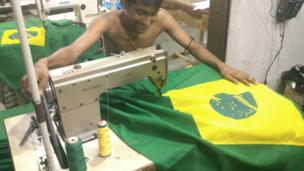 A worker stitches a flag in a Dhaka factory