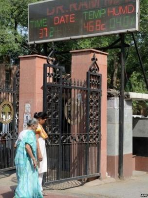 Indian residents walk past an electronic display board showing the current temperature in New Delhi on June 6, 2014