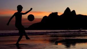 Young boy juggles a football on Ipanema Beach, Brazil. 9 June 2014