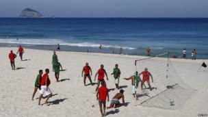 People playing football on beach