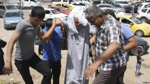 An elderly man is assisted at a checkpoint on the outskirts of Erbil on 10 June 2014.