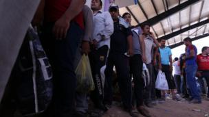 Iraqi men queue at a Kurdish checkpoint west of Erbil, on 10 June 2014