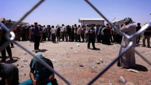 Iraqi families fleeing violence in the northern Nineveh province gather at a Kurdish checkpoint west of Erbil, on 10 June 2014