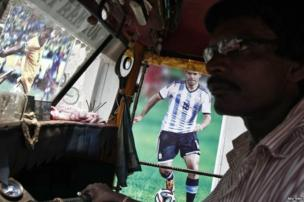 An auto rickshaw driver waits for passengers in front of a wall decorated with pictures of Brazilian and Argentine soccer players in Kolkata