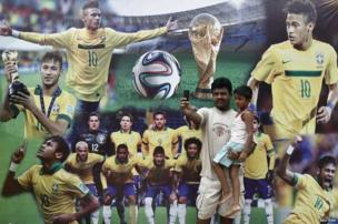 A football fan takes a selfie with a child in front of pictures of Brazilian soccer players along a city road.