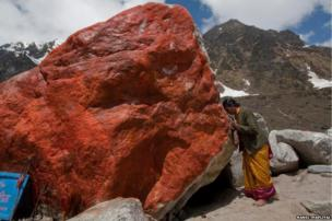 A pilgrim offers prayers to a large stone with its side painted saffron. The rock helped divert flood waters away from the temple in Kedarnath last year, that's why many today believe it to be sacred.