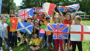 Children in Oxford hold commonwealth flags