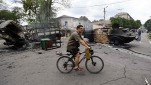 A resident cycles past destroyed vehicles at the site of fighting in the eastern Ukrainian port city of Mariupol, 13 June 2014