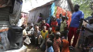 People in a displacement camp watching football on television outside, Mogadishu, Somalia - Thursday 12 June 2014