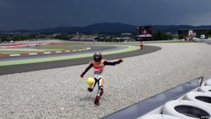 Honda MotoGP rider Marc Marquez of Spain kicks a soccer ball as he celebrates with supporters after winning the Catalunya Grand Prix in Montmelo, near Barcelona, June 15