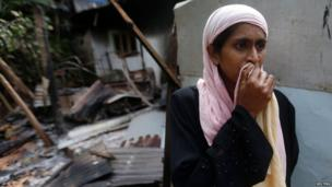 A Muslim woman stands next to her burnt house after a clash between Buddhists and Muslims in Aluthgama June 16