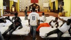 """In this picture taken Sunday, June 15, 2014, migrants from Africa are temporarily sheltered in the Catholic church of St. Curato D""""Ars in Palermo, Sicily, Italy"""