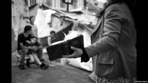 A woman holds a Bible on Plaza Bolivar in Bogota