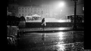 A displaced man walks across Plaza Bolivar in the rain