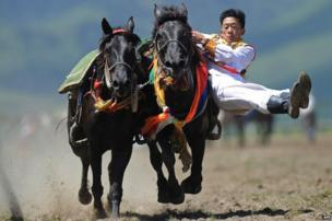 A rider in ethnic group costume competes in a traditional horseback riding event in Hongyuan county, China