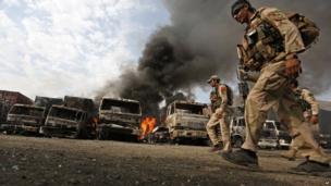 Afghan policemen investigate the scene of a suicide attack in Torkham, Nangarhar province, Afghanistan. 19 June 2014