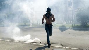 A Kosovo Albanian runs away from tear gas grenades fired by riot police during clashes on 22 June 2014 in the divided town of Mitrovica.