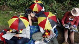 Visitors wearing umbrella hats sit and queue to enter the grounds on the first day at the All England Lawn Tennis Championships in Wimbledon, London, on 23 June 2014