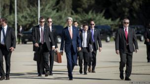 US Secretary of State John Kerry walks with his bodyguards towards a plane at Jordan's Queen Alia International Airport in Amman, Jordan