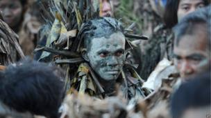 "Devotees covered in mud and wearing costumes made from banana leaves attend mass as they take part in a religious festival in honor of St. John the Baptist, also known locally as the ""mud people"" festival in Aliaga, Nueva Ecija province, north of Manila, on June 24, 2014"