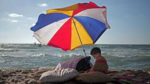 In this Monday, June 23, 2014 photo, a Palestinian boy sits under an umbrella as he and others enjoy a summer day at the beach of Gaza City