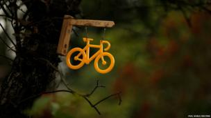 A plastic yellow bicycle-shaped decoration is attached to a tree outside a house on the route of the Tour de France near Ripponden, northern England.