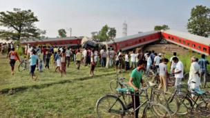 People gather around a passenger train that derailed near Chhapra town in Bihar, India