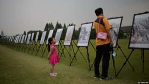 A South Korean girl listens to her grandfather at a photographic exhibition of the Korean War at the National Cemetery in Seoul