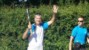 Teacher Mr Foley with the baton as it leaves Newbattle