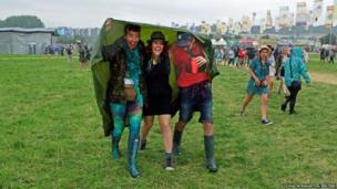 Festival goers react as the rain starts to fall