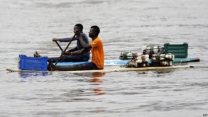 Two fishermen sit on wooden boards at the Ebrie Lagoon in Ivory Coast on 23 June 2014