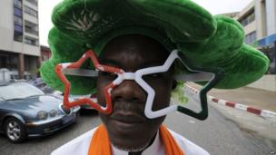 An Ivory Coast supporter dressed in national colours poses in Abidjan on 24 June 2014