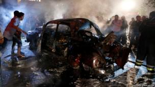 People gather at the site of an explosion at the southern suburbs of the Lebanese capital Beirut