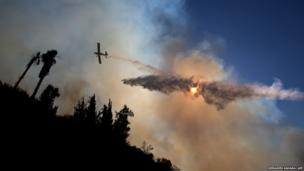 An aeroplane drops water over Jerusalem forest in an attempt to control wildfires
