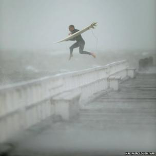 A surfer jumps off the pier into Port Phillip Bay