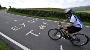 A cyclist approaches a slogan painted on the roads of the Yorkshire Stage 2 route of the Tour de France near Sheffield