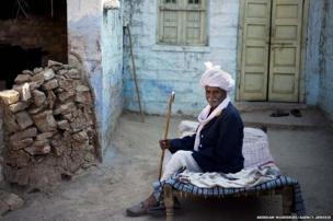 Jodha Ram Bishnoi sitting in front of his house at guda bishnoi village wearing traditional bishnoi dress. Jodhpur, Rajasthan, India.