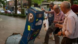 Residents of the Madrid suburb of Carabanchel knock over a cardboard replica of a parking meter (1 July 2014)