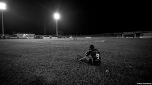 A player for Gaviao Kyikateje Football Club sits on the pitch