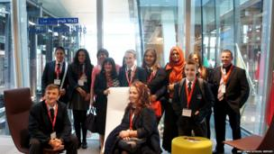 School Reporters, teachers and anti-bullying ambassadors from Appleton Academy pose in front of the glass wall at Facebook's London headquarters