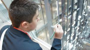 Thomas writes on the glass wall at the Facebook offices