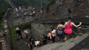 Visitors walk down a steep section on a restored part of the Great Wall of China, at Mutianyu, north of Beijing