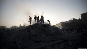 Palestinians inspect damaged houses after an Israeli missile strike hit Gaza City