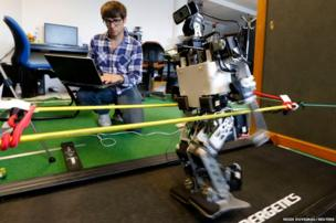 A member of the Rhoban project's team checks functions of a humanoid robot